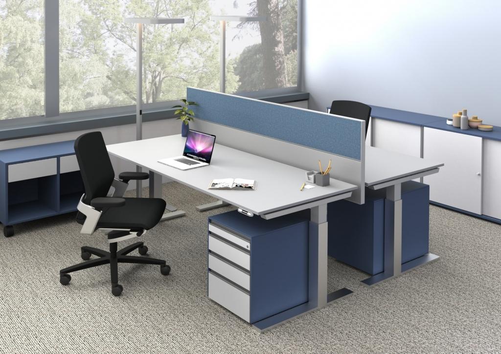 Seitenansicht Doppelarbeitsplatz ausgestattet mit Sitz-Steh-Tischen s476, getrennt durch Tischpaneel mit blauem Pinnwandstoff sowie Stauraum in Form von Rollcontainern.