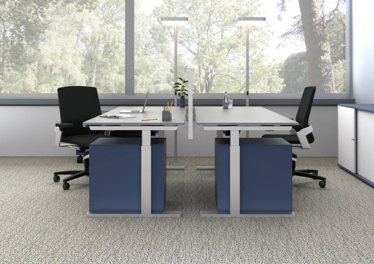 Doppelarbeitsplatz ausgestattet mit Sitz-Steh-Tischen s476, getrennt durch Tischpaneel mit blauem Pinnwandstoff.