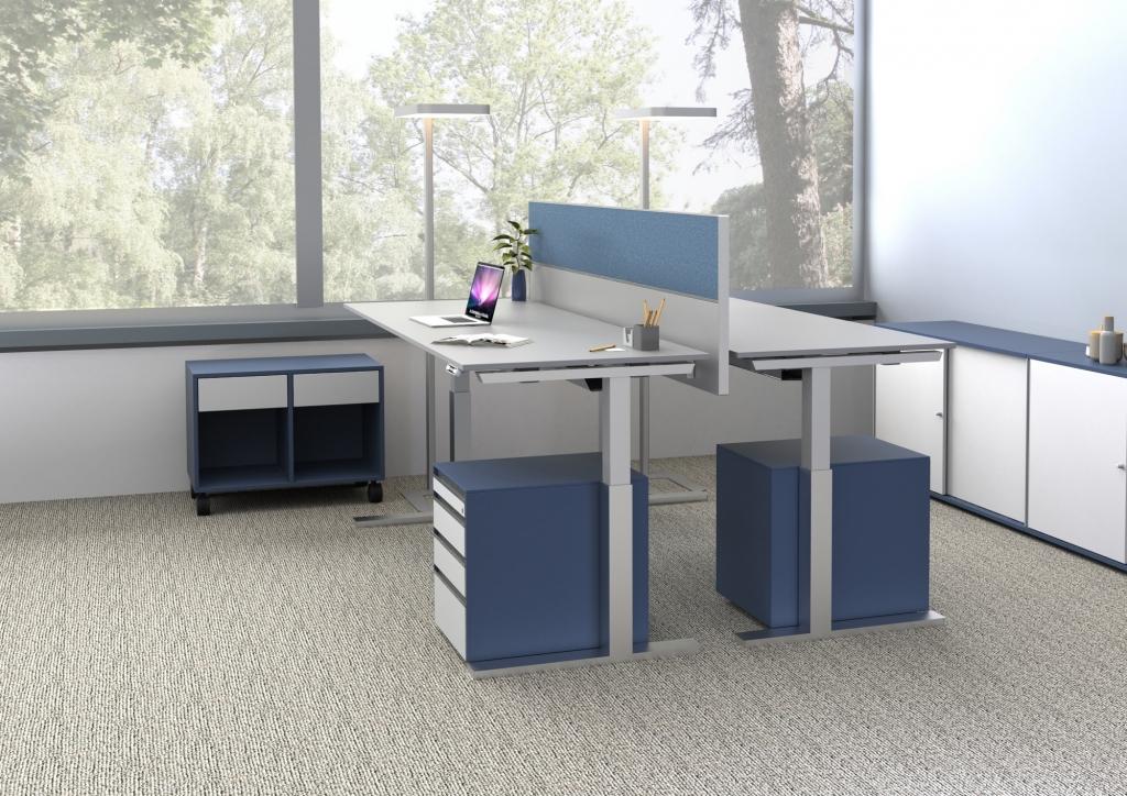 Doppelarbeitsplatz ausgestattet mit Sitz-Steh-Tischen s476 in erhöhter Position, getrennt durch Tischpaneel mit blauem Pinnwandstoff.