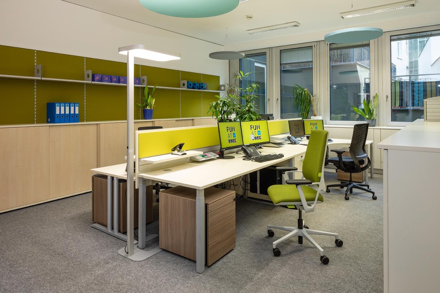 Open Space Office mit Sichtschutz mit Pinnwand in grün und Rollcontainer in Holzoptik.