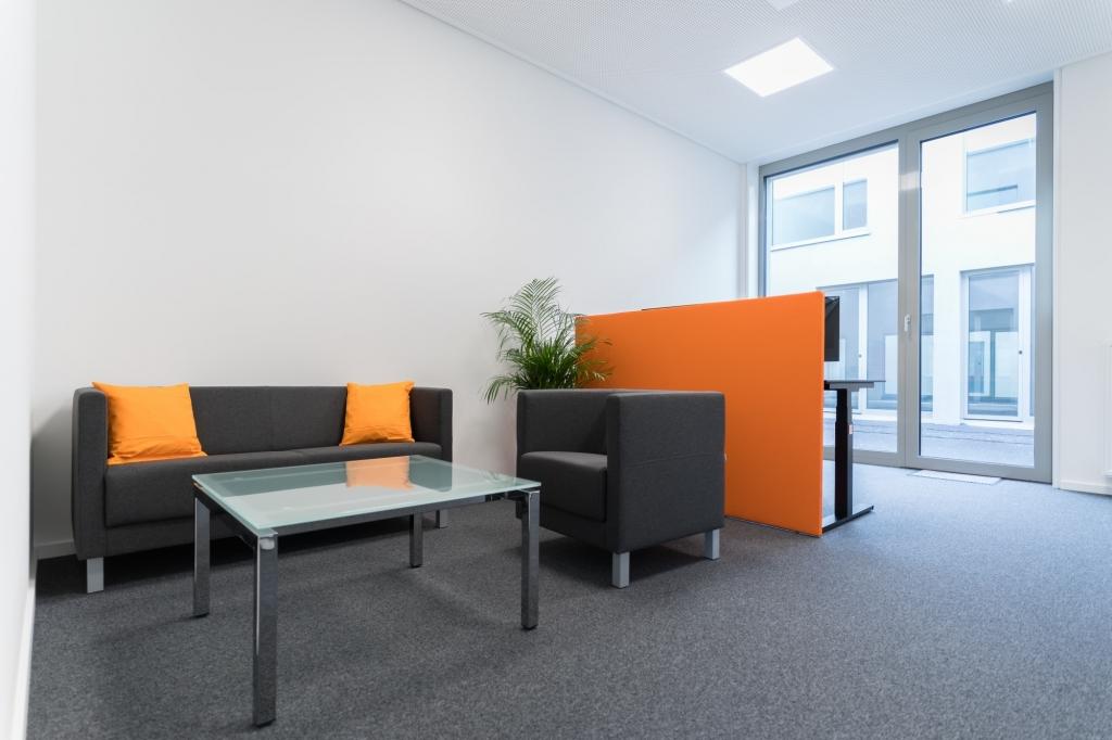 Loungebereich in Unternehmensfarben sowie Sichtschutz und Einzelarbeitsplatz mit Sitz-Steh-Tisch.