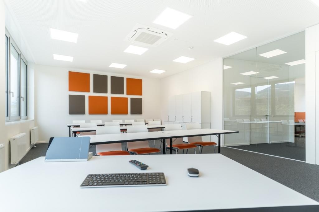 Seminarraum mit Akustikwandbildern in Unternehmensfarben, Stühlen mit weißer Sitzschale und Sitzpolster passend zum Raumdesign sowie Drehtürenschänken mit Schloss.
