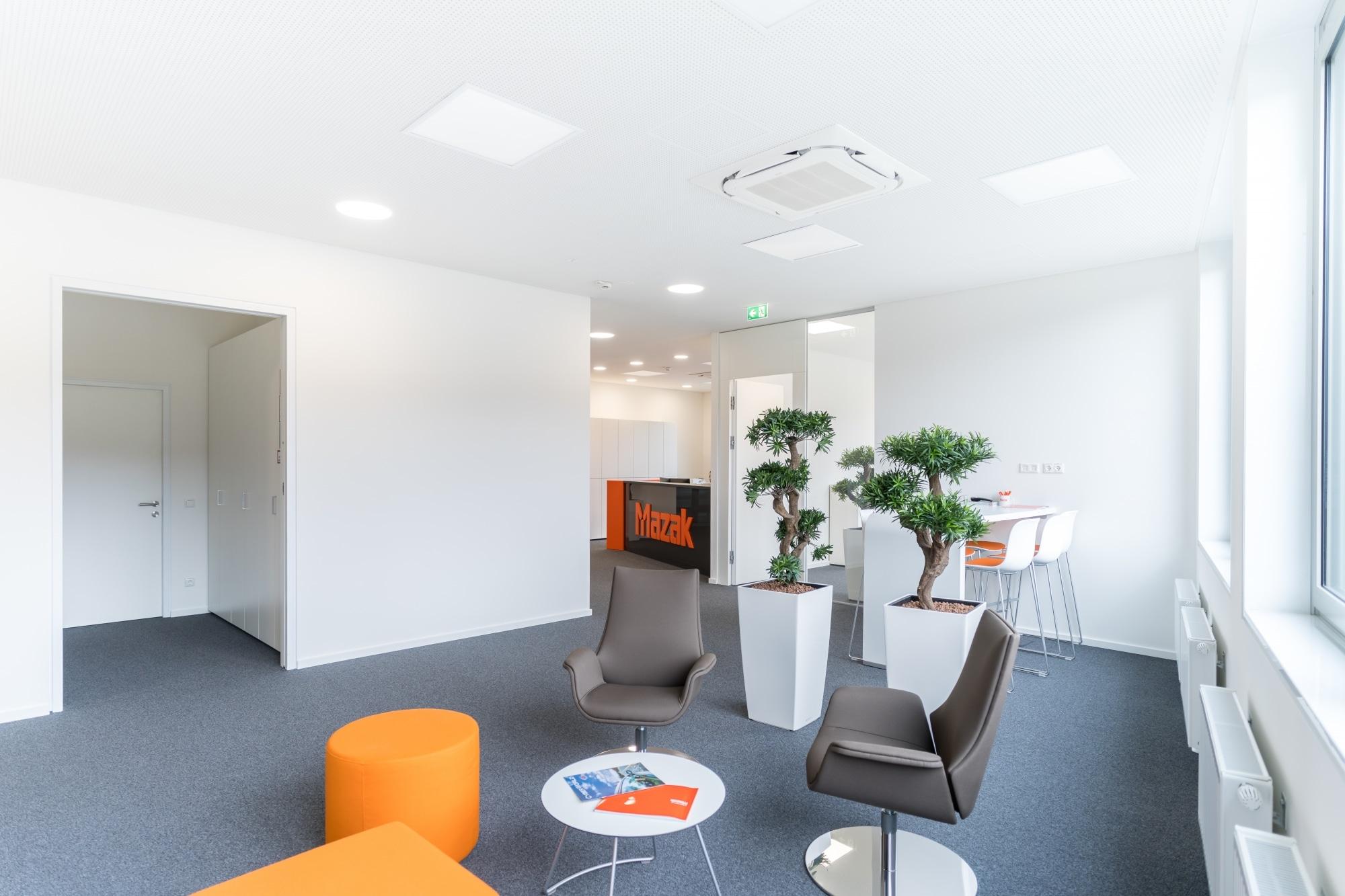 Loungebereich mit bequemen Besucherstühlen und Hockern. Bürobegrünung als Trenner zu Besprechungsbereich mit Stehtisch und Barstühlen.