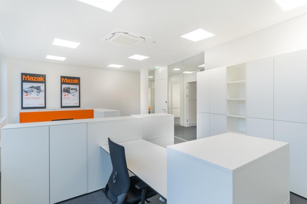 Arbeitsplatz mit Sitz-Steh-Tisch mit weißer Tischplatte und Vollpolster-Drehstuhl in schwarz sowie Push-to-open Drehtürenschränke und Regale in Melamin weiß.