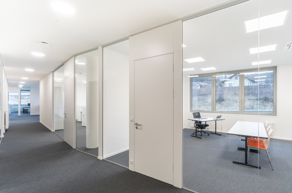 Glastrennwände und Melamintüren in weiß zur Schaffung von Räumen zwischen Wänden in einem Großraumbüro.
