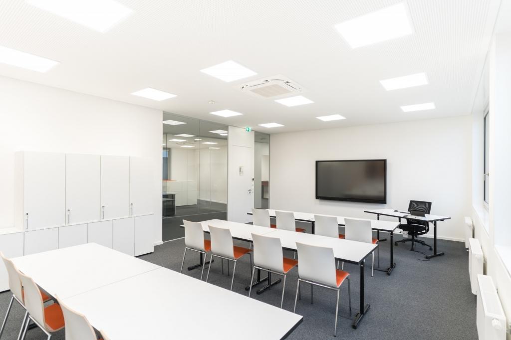 Seminarraum mit Rechtecktischen mit schwarzen Tischgestell und einer Tischplatte in Melamin grau sowie Stühlen in den Unternehmensfarben und einer Medienausstattung für moderne Präsentationen.