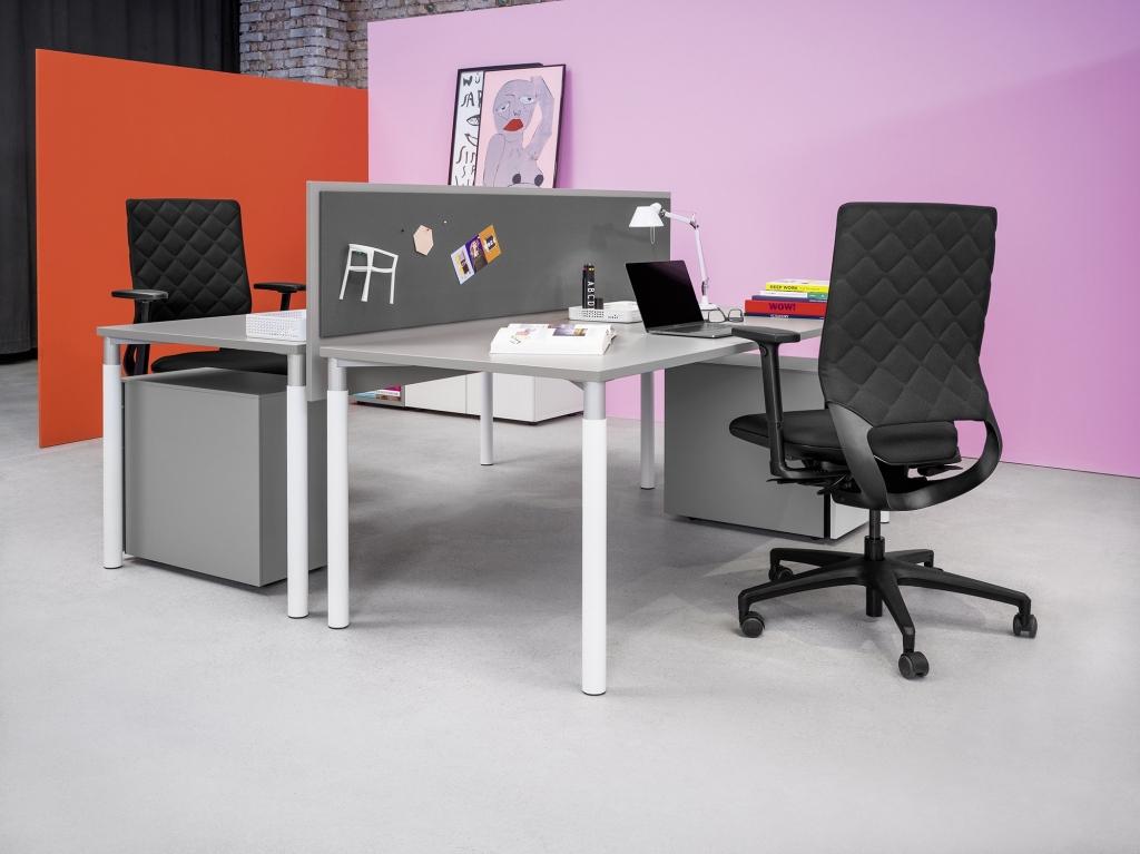Doppelarbeitsplatz mit Tischen der Serie s100 getrennt durch Tischpaneel mit Pinnwand.