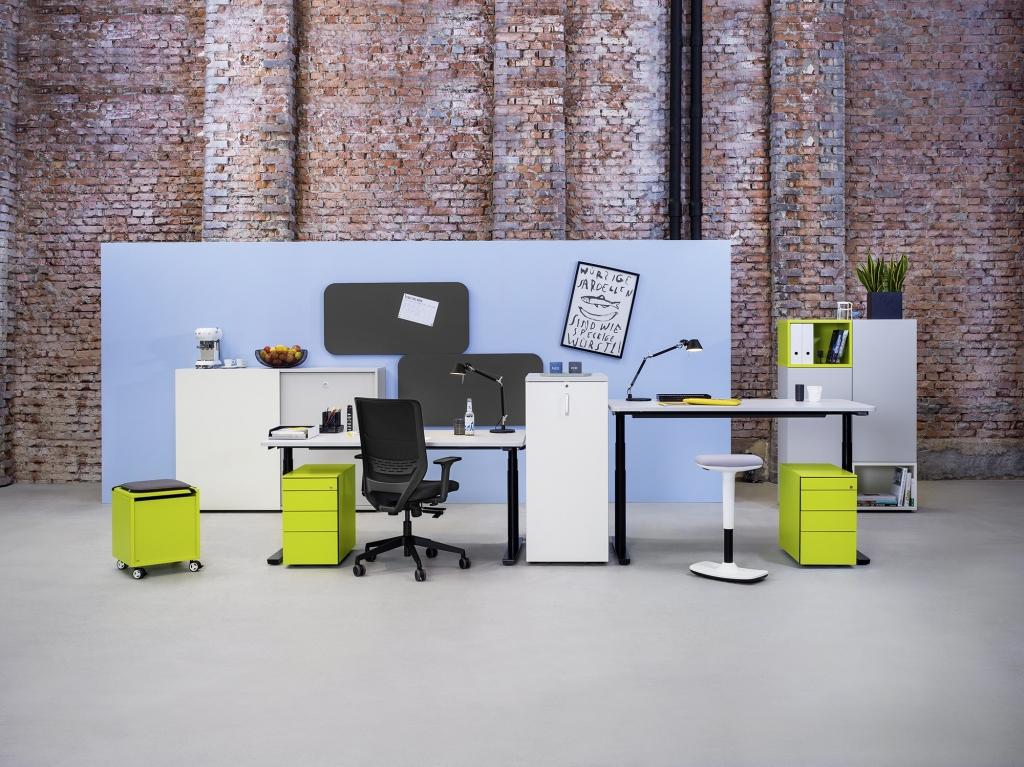 Büroszene mit Sitz-Steh-Tischen der Serie s100 mit Tischgestell in schwarz und Tischplatte in Melamin weiß getrennt durch einen Apothekerschrank.