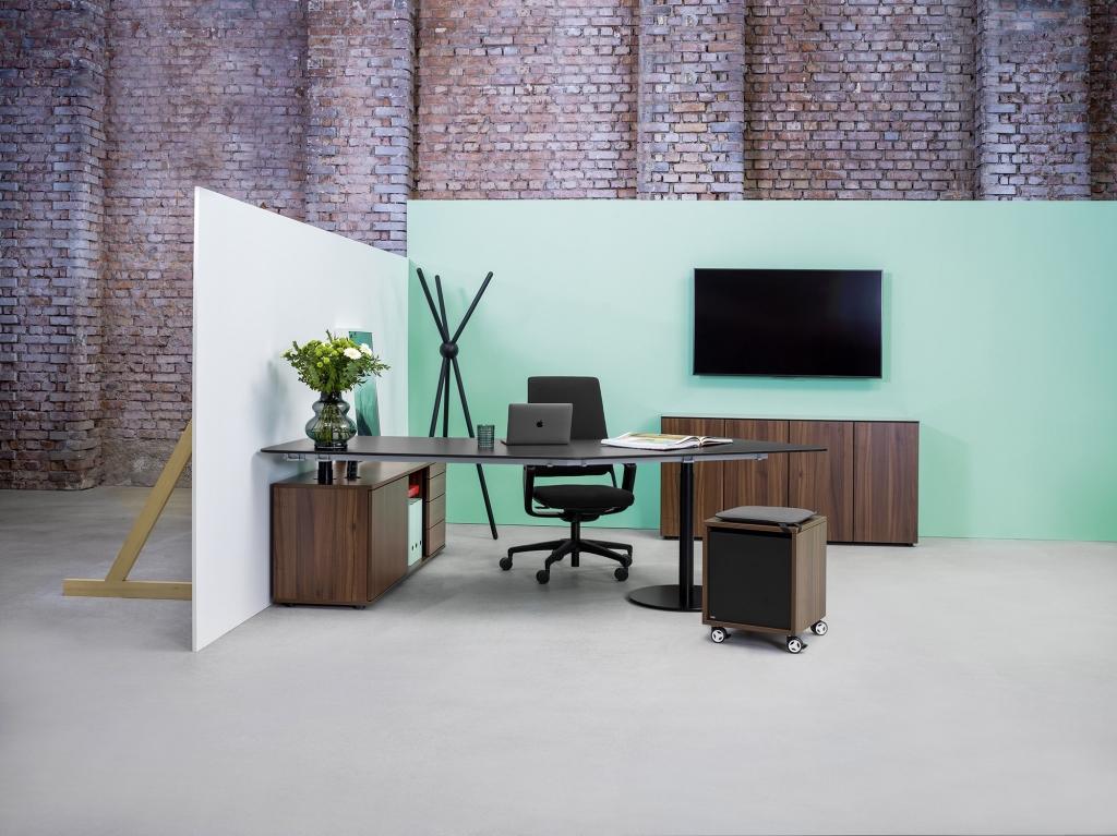Ambientebild mit Sitz-Steh-Tisch der Serie s100 mit Tischgestell in Schwarz und Tischplatte und Stauraum in Nussoptik sowie Drehtürenschrank in Nussoptik und dazu passenden Bulli.