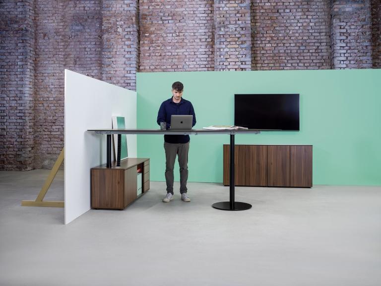 Ambientebild Consultertisch s570 in Sitz-Steh-Tisch Variante mit schwarzem Tischgestell und Stauraum sowie Tischplatte in Melamin Nussoptik.