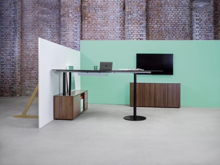 Arbeitsplatz Consultertisch s570 in Sitz-Steh-Tisch Variante mit schwarzem Tischgestell und Stauraum sowie Tischplatte in Melamin Nussoptik.