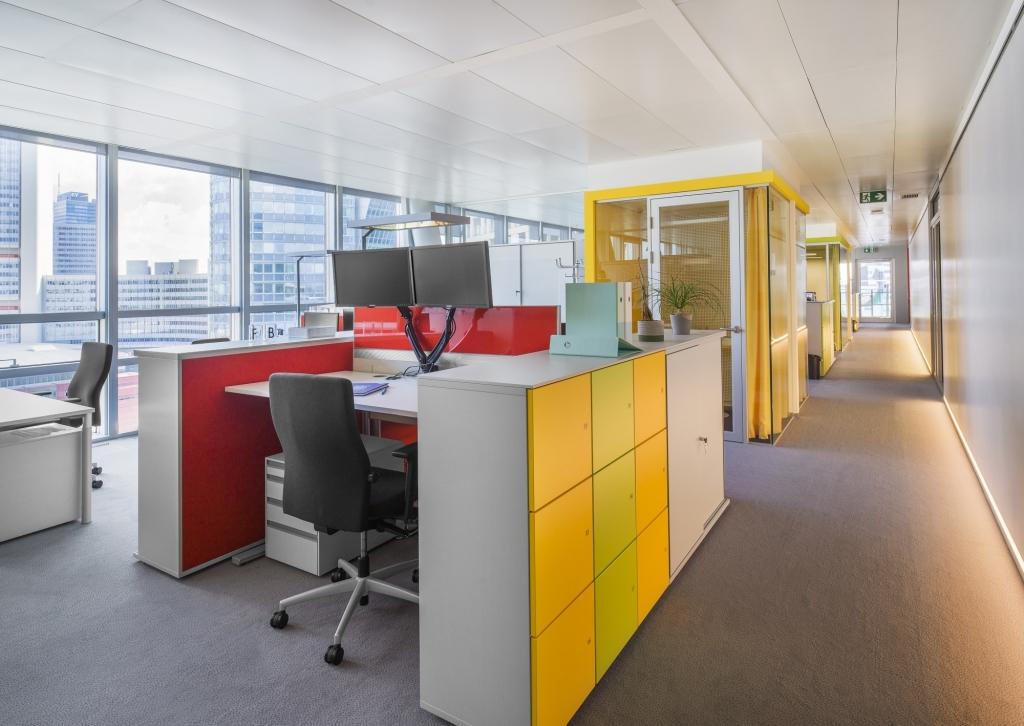 Offener Bürobereich unterbrochen von kleinen Meetingboxen in gelb. Ausgestattet mit Doppelarbeitsplätzen sowie Schiebetürenschränken und Schließfachschränken.