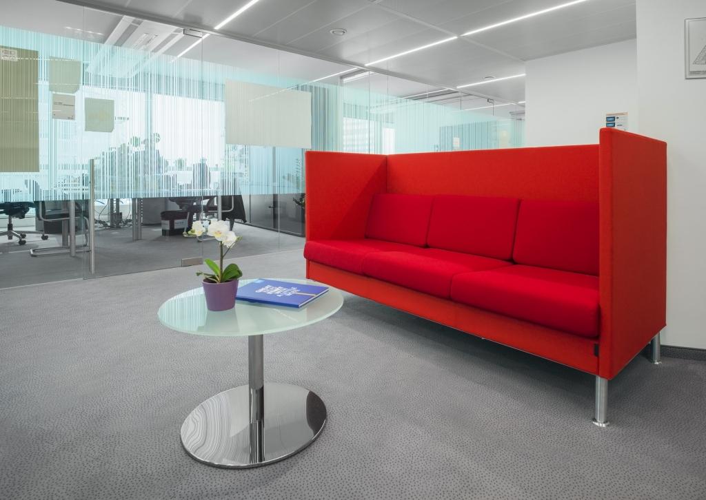 Offener Loungebereich mit Sitzbank in rot und Glastisch mit verchromtem Tischbein.