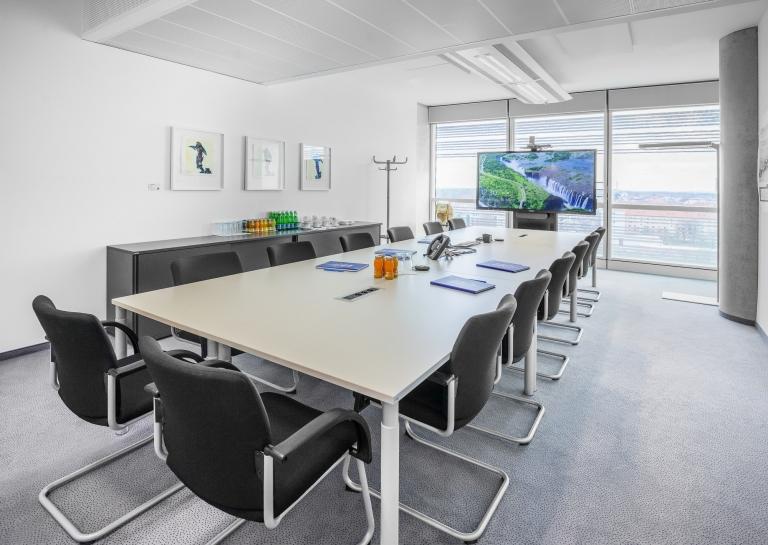 Meetingraum mit Tischen der Serie s100 inklusive integrierter Stromanschlüsse und bequemen Besucherstühlen mit schwarzer Polsterung.