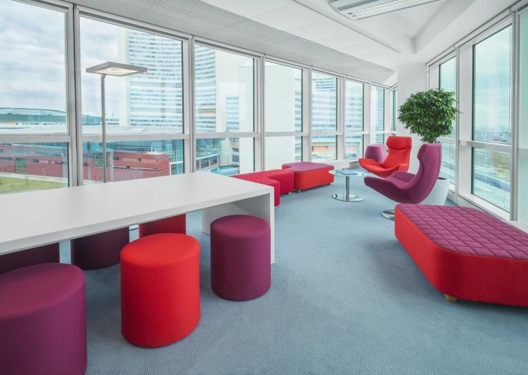 Loungebereich mit roten Loungemöbel sowie Meetingbereich mit Hockern in rot und Tisch mit weißer Oberfläche.