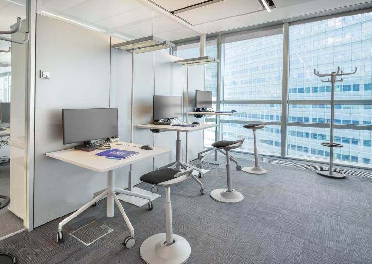 Arbeitsplatzsharing-Bereich mit Tischen auf Rollen inklusive ergonomischen Hocker.