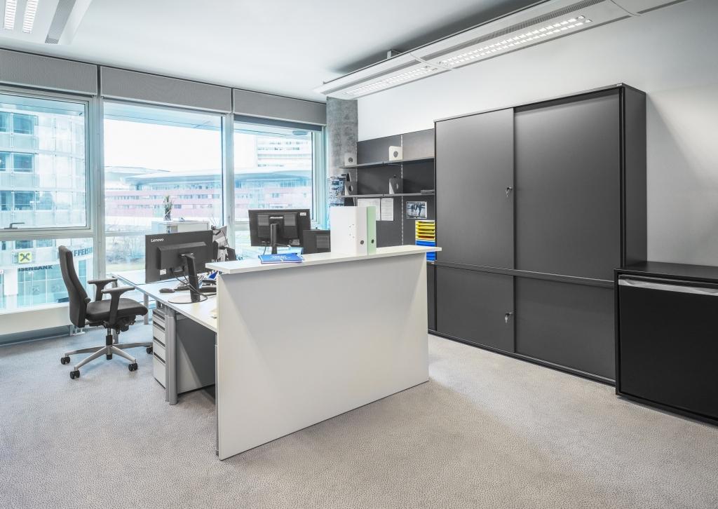 Empfangsbereich mit Doppelarbeitsplatz und integriertem Empfangspult in bright grey und Drehtürenschränke sowie Akustik-Pinnwände in dark grey.