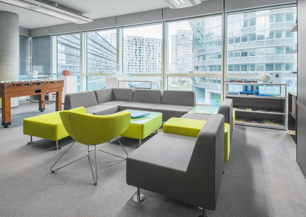 Ambientebild eines Loungebereichs für Mitarbeiter mit einer großen Couch in grün und grau sowie einem Fußballtisch.