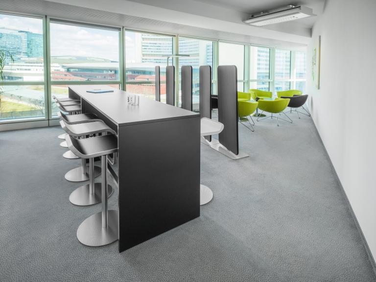 Raum mit durch Akustikaufsteller voneinander getrennte Meetingbereiche. Zum einen ein Stehtisch mit Barhockern in schwarz, zum anderen eine Sitzgruppe mit bequemen Loungesessel in grün.