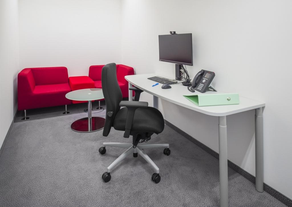 Ausweichraum für zwei Personen Meetings oder Arbeitsplatz für wenige Stunden. Ausgestattet mit einer roten Couch sowie Glastisch und Arbeitstisch s110 in schmaler Version sowie Drehstuhl.
