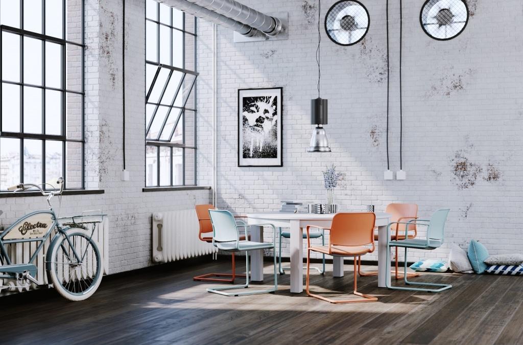 Industriedesign Büro mit Meetingbereich ausgestattet mit Besucherstühlen Zoo der marke Profim mit Freischwingergestell. Die Besucherstühle sind einfärbig, vom Gestell über das Sitzkissen, bis hin zur Rückenlehne in orange beziehungsweise hellblau gehalten.