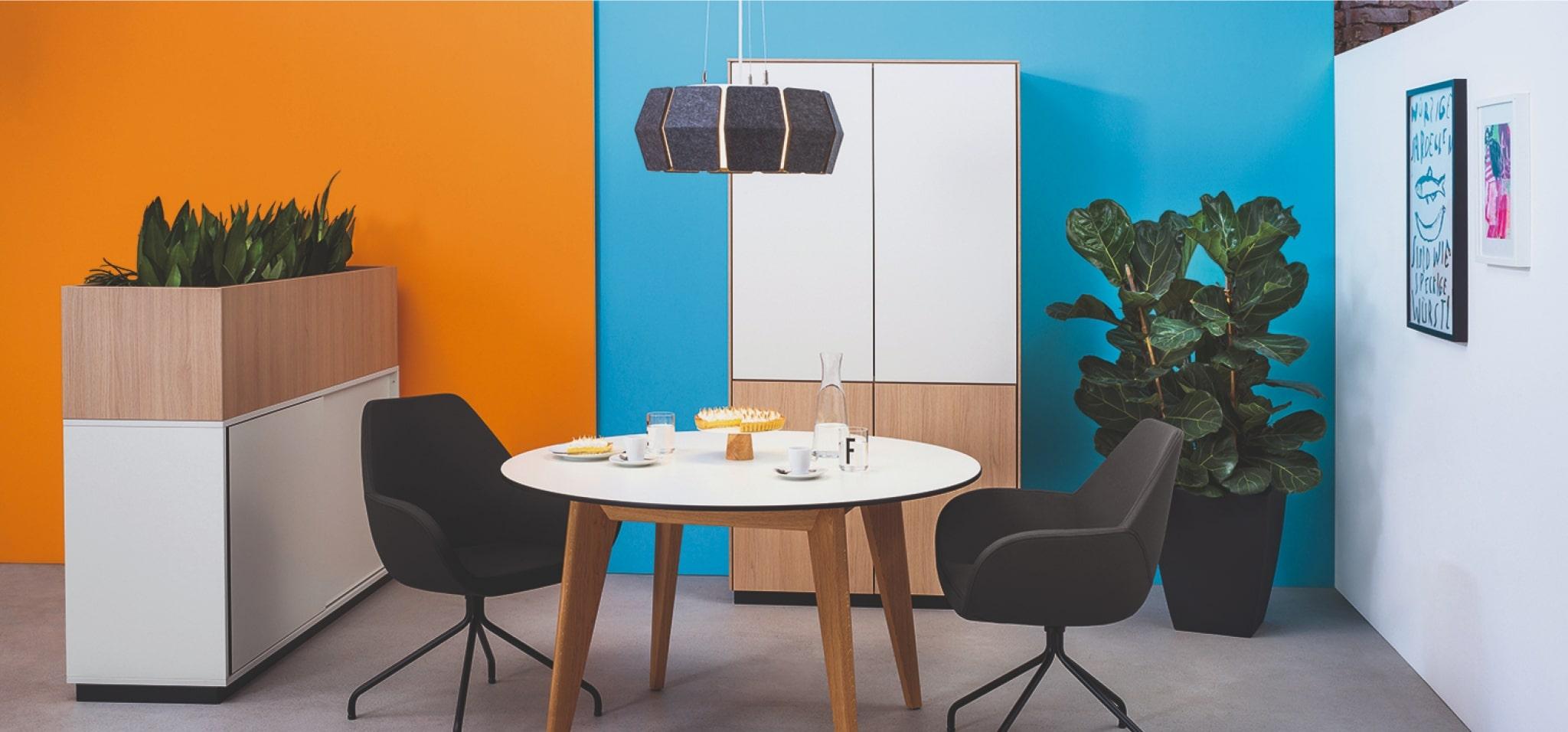Rundtisch m600 mit Tischgestell aus Holz und Compactplatte in weiß mit schwarzer Tischkante sowie Drehtürenschrank mit geteilter Schrankfront in Melamin weiß und Holzoptik.