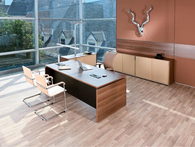 Ambientebild Managerbüro mit Arbeitstisch in Holzoptik mit Stauraum in Brauntönen gehalten.