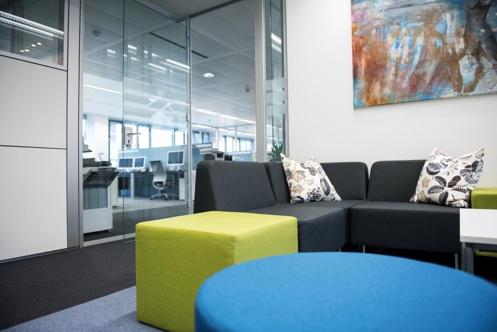 Loungebereich mit farbigen Loungemöbeln und Trennwandsystem RS mit Tür für den Zugang in das Großraumbüro.