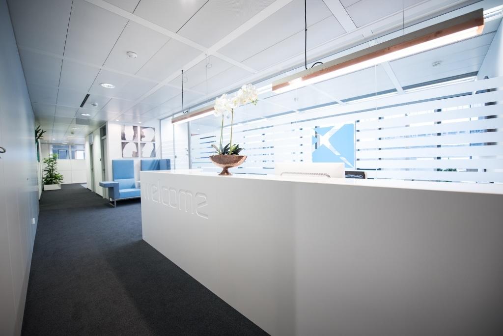 Empfangsbereich mit Pult der Produktserie s800 aus MDF weiß lackiert mit Glasplatte.