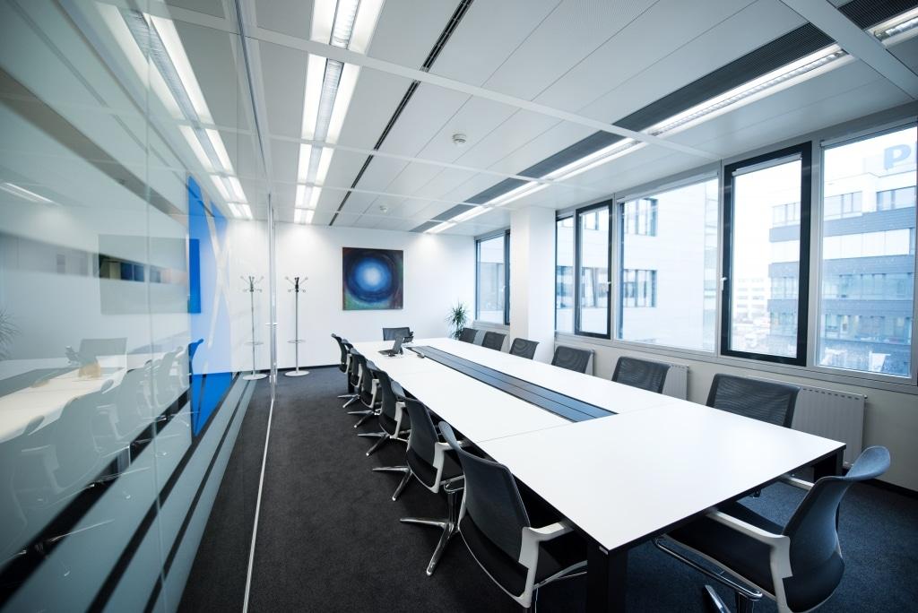 Konferenzraum mit Konferenztisch s180 mit schwarzem Tischgestell und weißer Tischplatte sowie Trennwänden RS11 mit Beklebung.