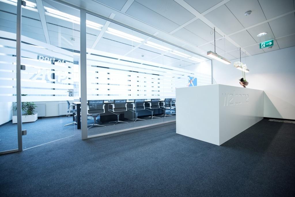 Empfangsbereich mit Trennwand und Trennwandtür RS11 zum angrenzenden Konferenzraum. Empfangspult der Produktserie s800 aus MDF weiß lackiert mit Glasplatte.