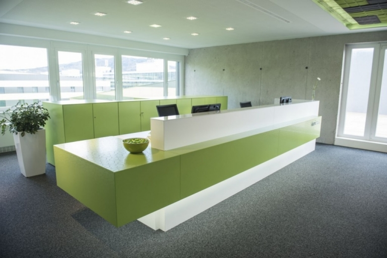Empfangsbereich in weiß und grün mit Drehtürenschränke im Hintergrund.