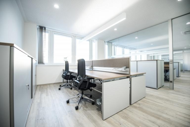 Doppelarbeitsplatz mit Arbeitstischen der Serie s500 in weiß und Tischplatte Melamin in Nussoptik sowie Sichtschutz mit Organisationsschiene und Pinnfläche in beige.