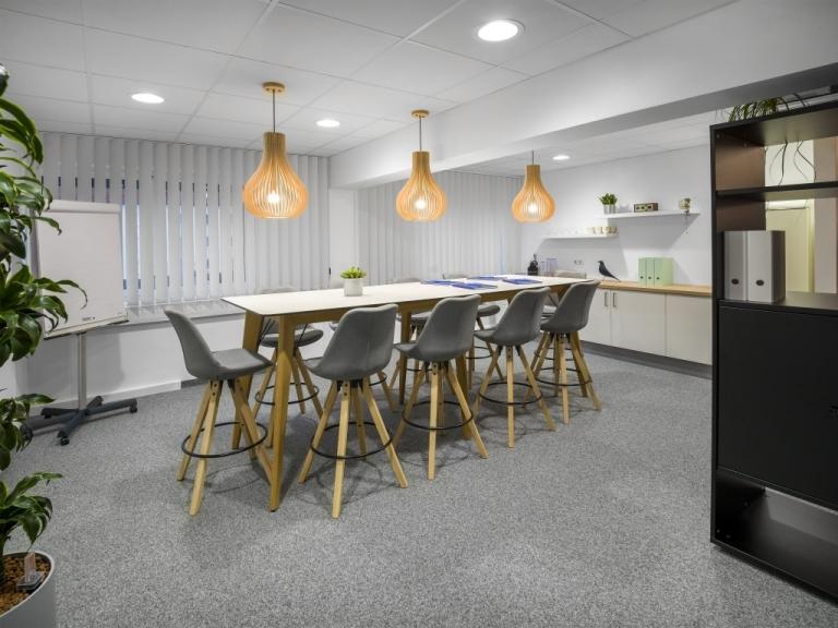 Besprechungsraum mit Stehtisch m600 mit Tischgestell aus Eichenholz und weißer Tischplatte sowie Barstühlen mit modernen Holzgestell und gepolsterter, grauer Sitzschale.