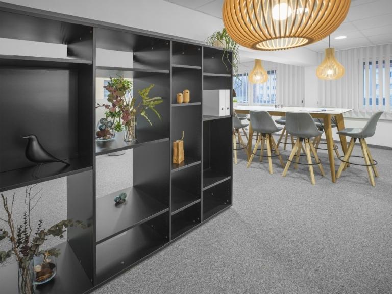 Box Regal als Raumtrenner in Meetingraum. Im Hintergrund steht der Meetingtisch m600 mit Eichengestell und Tischplatte in weiß.