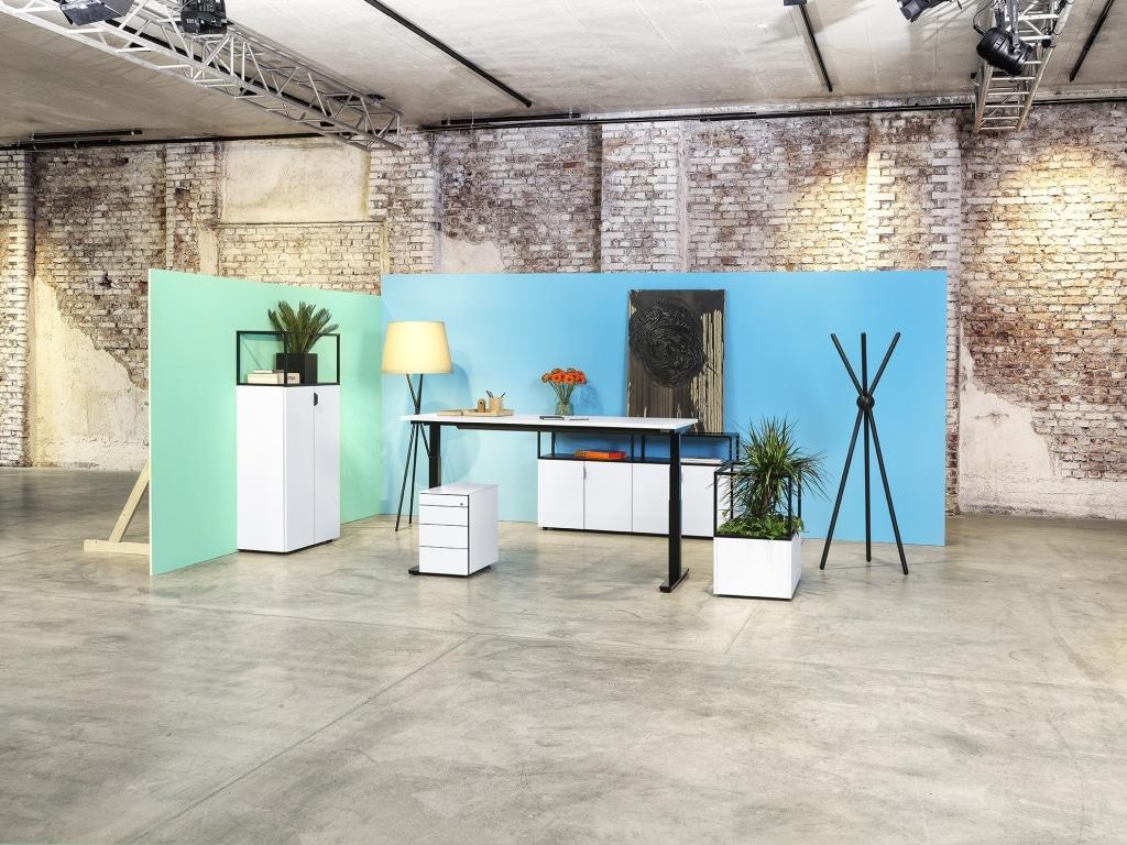 Bürogestaltung mit Stauraumsystem Framework und Sitz-Steh-Tisch s171 mit weißen Melaminoberflächen und Tischgestell sowie Modulrahmen in schwarz.